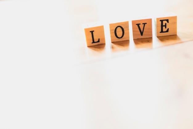 Exprima o amor em dados de madeira e no fundo branco. Foto Premium