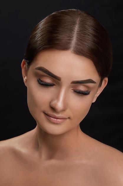 Extensões de cílios. pestanas falsas. closeup da bela jovem modelo feminino com pele macia suave e maquiagem facial profissional. retrato de uma garota sexy com cílios longos falsos e maquiagem perfeita. Foto Premium