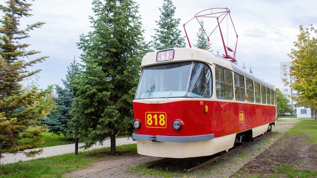 Exterior de um bonde vintage vermelho e branco na ferrovia como uma exposição com número 818, vegetação ao redor, chisinau, moldávia Foto Premium