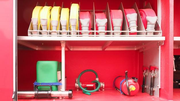 Extintor e mangueira dos acessórios dos sapadores-bombeiros, ferramentas e equipamento no carro de bombeiros vermelho. Foto Premium