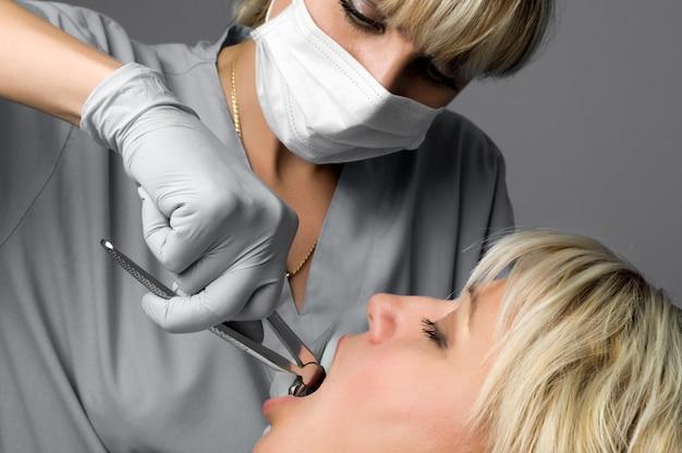 Extração dentária com fórceps, instrumento odontológico especial para remoção de dentes Foto Premium