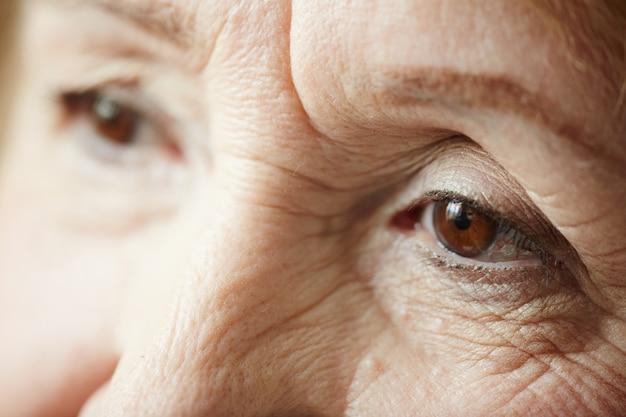 Extremo close-up da triste mulher idosa Foto gratuita