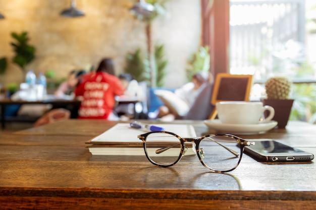Eyeglasses e telefone celular selecionados do foco na tabela de madeira. Foto Premium
