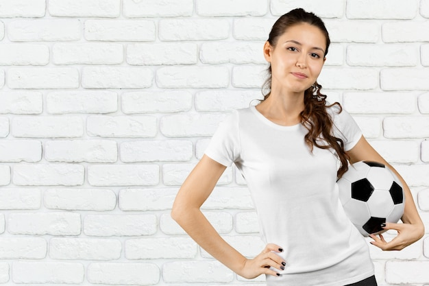 Fã de futebol. jovem mulher bonita segurando bola de futebol sobre fundo isolado Foto Premium