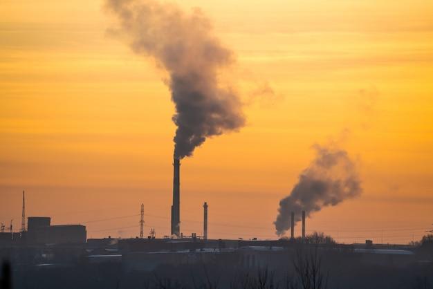 Fábrica com canos e fumaça ao amanhecer do sol. Foto Premium