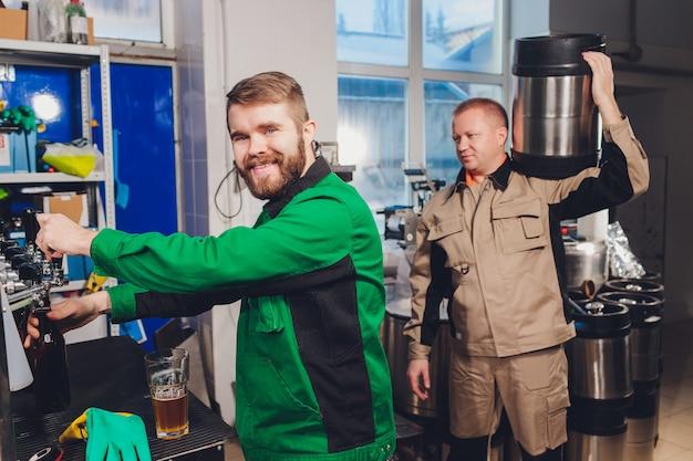Fábrica de cervejaria derramando cerveja em garrafas de vidro nas linhas transportadoras. trabalho industrial, produção automatizada de alimentos e bebidas. trabalho tecnológico na fábrica. Foto Premium