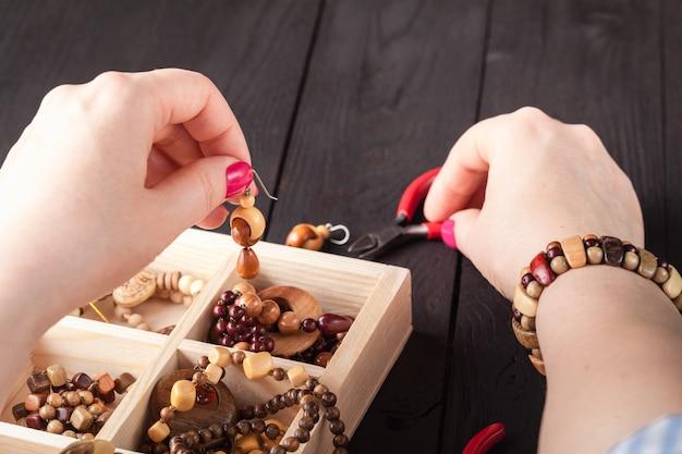 Fabricação de jóias artesanais. caixa com miçangas na mesa de madeira velha. Foto Premium