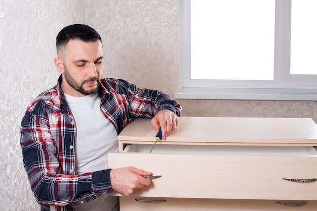 Fabricante de móveis masculino monta móveis em um apartamento Foto Premium