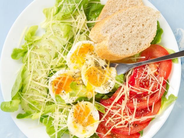 Faça dieta a salada com ovos cozidos, queijo e vegetais macios - tomates, alface. Foto Premium