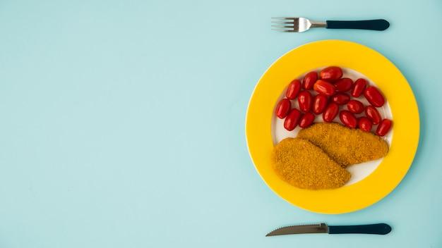 Faca, garfo e prato com peito de frango e tomate na mesa azul Foto gratuita
