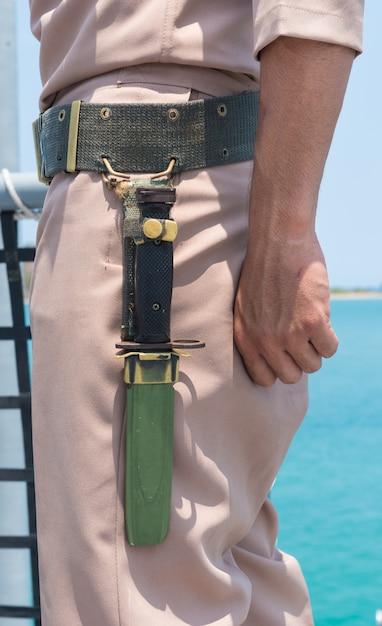 Faca perto da mão do marinheiro lateral na vista para o mar do navio exterior. Foto Premium
