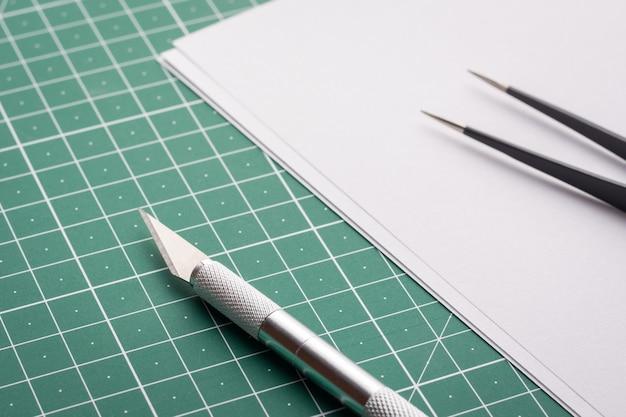 Faca profissional e pinça perto de papel branco em branco na esteira de corte Foto Premium