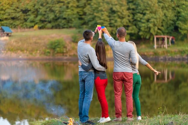 Faça um piquenique com os amigos no lago perto da fogueira. amigos tendo caminhada natureza piquenique. caminhantes relaxantes durante o tempo de bebida. piquenique de verão. diversão com os amigos Foto Premium