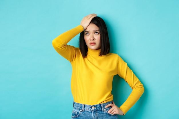 Facepalm de mulher asiática cansada e triste, suspirando e olhando para cima angustiado, sentindo-se incomodado em pé contra um fundo azul. Foto Premium