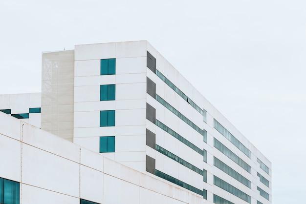 Fachada de uma construção industrial do cimento branco com linhas retas e fundo do céu. Foto Premium