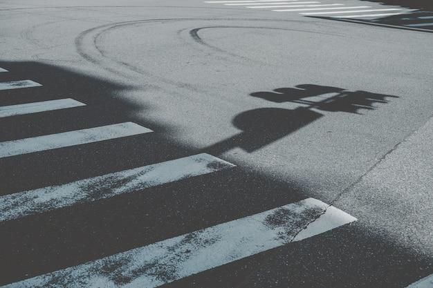 Faixa de pedestres ao lado da sombra da placa de rua Foto gratuita