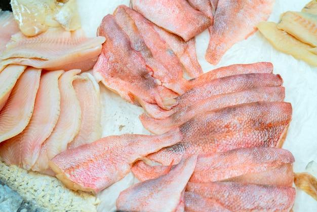 Faixa do badejo dos peixes frescos em um contador do gelo em um supermercado. Foto Premium