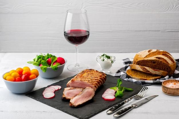Faixa grelhada da carne de porco com os tomates frescos e o raddish servidos com vidro do vinho tinto. Foto Premium
