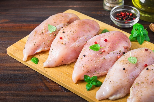 Faixas cruas da galinha em uma placa de corte na perspectiva de uma tabela de madeira. Foto Premium