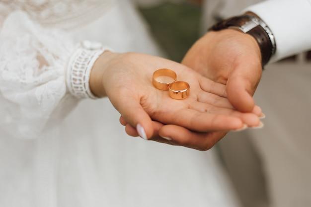 Faixas douradas nas mãos do noivo e noiva Foto gratuita