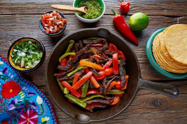 Fajitas de carne em uma panela com molhos comida mexicana Foto Premium