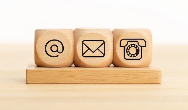Fale conosco conceito. blocos de madeira com ícones de email, mail e telefone. página do site entre em contato ou e-mail marketing Foto Premium