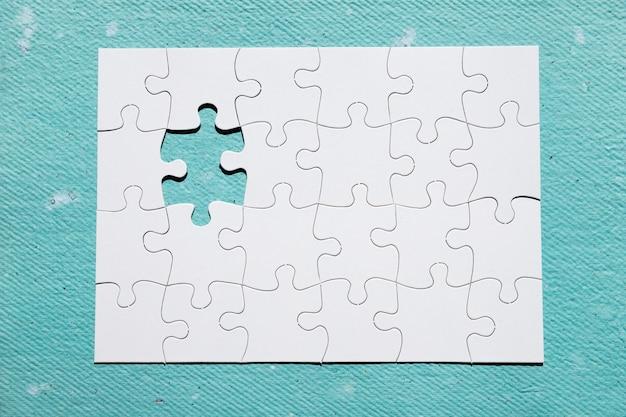 Falta pedaço de quebra-cabeça no pano de fundo texturizado azul Foto gratuita