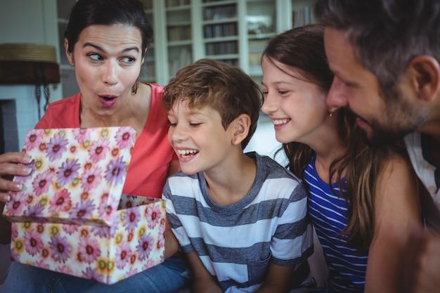 Família abrindo o presente surpresa na sala de estar Foto Premium