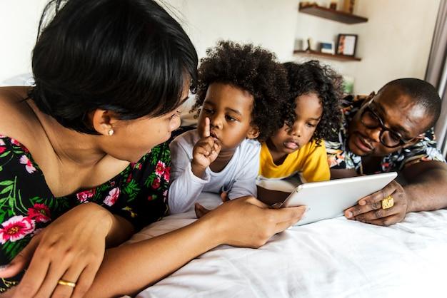 Família africana na cama usando um tablet Foto Premium