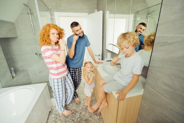 Família agradável e agradável escovando os dentes Foto Premium