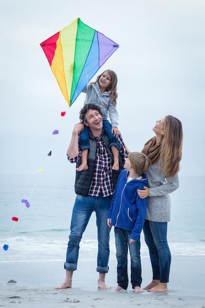 Família alegre com pipa na costa do mar Foto Premium