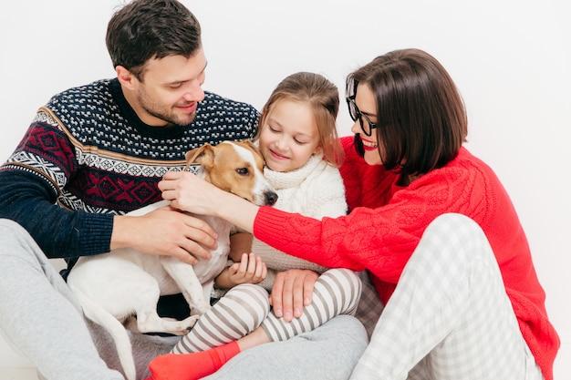 Família amigável se abraçam e lisonjeiam seu cão, se divertem, posam juntas Foto Premium