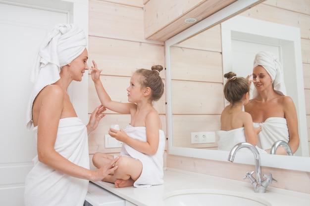 Família amorosa feliz mãe e filha com toalhas cuidam da pele e apliquem hidratante no rosto no banheiro branco. Foto Premium