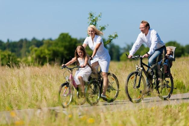 Família andando de bicicleta no país no verão Foto Premium