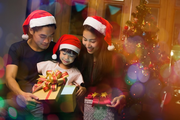 Família asiática abrindo uma caixa de presente no dia de natal feliz Foto Premium