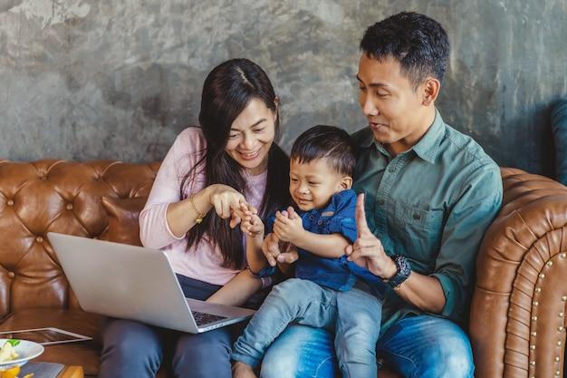 Família asiática, com, filho, é, olhar, a, caricatura, através, tecnologia, laptop, e, jogando junto Foto Premium