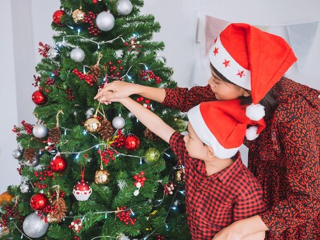 Família asiática comemorando o natal em casa, mãe e filho decoram a árvore de natal Foto Premium