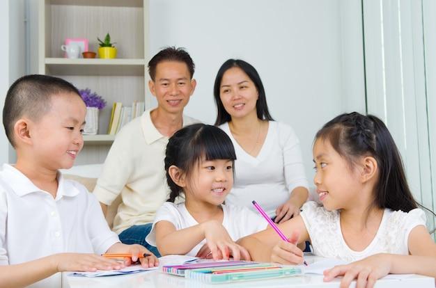 Família asiática fazendo lição de casa da escola na sala de estar Foto Premium