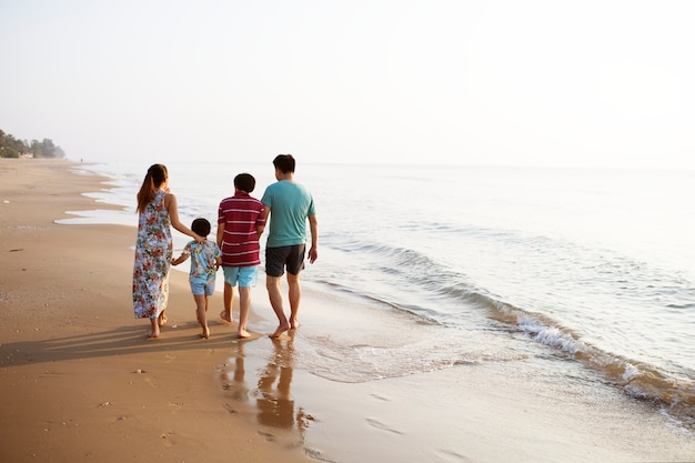 Família asiática na praia Foto gratuita