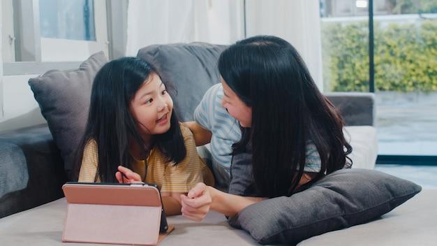 Família asiática nova e filha felizes usando a tabuleta em casa. mãe japonesa relaxar com a menina assistindo filme deitado no sofá na sala de estar em casa. mãe engraçada e criança adorável estão se divertindo. Foto gratuita