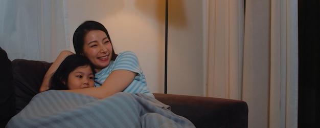 Família asiática nova e filha que olham a tevê em casa na noite. mãe coreana com menina feliz usando o tempo com a família relaxar deitado no sofá na sala de estar. mãe engraçada e criança adorável estão se divertindo. Foto gratuita