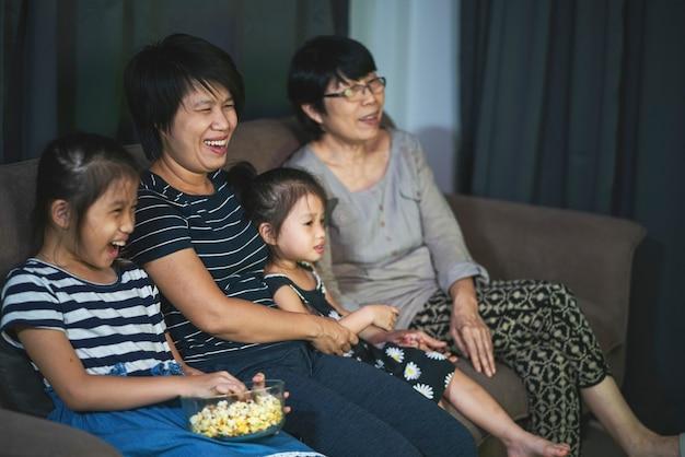 Família asiática sentada em um sofá aconchegante e comendo pipoca enquanto assiste a um filme em uma sala de estar em casa. entretenimento doméstico, família asiática e conceito de tempo juntos Foto Premium