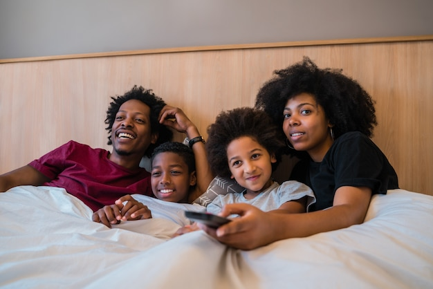 Família assistindo a um filme na cama em casa. Foto gratuita