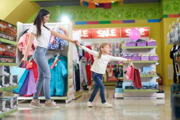 Família ativa mantendo sacos de papel e funcionando na loja Foto gratuita