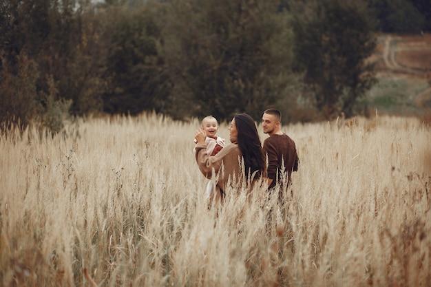 Família bonita e elegante, jogando em um campo Foto gratuita