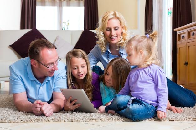 Família brincando com computador tablet em casa Foto Premium