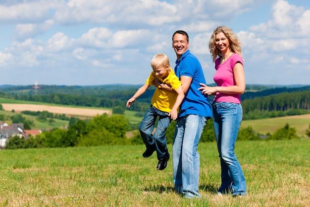 Família brincando no prado no verão Foto Premium