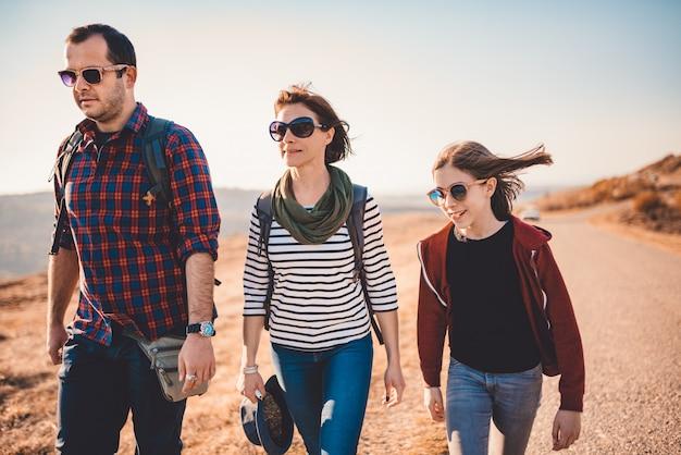 Família caminhando juntos pela estrada de asfalto em um dia ensolarado Foto Premium