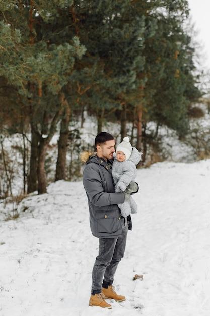 Família caminhando na neve se divertindo no parque de inverno em um dia ensolarado, abraçando-se e sorrindo Foto gratuita