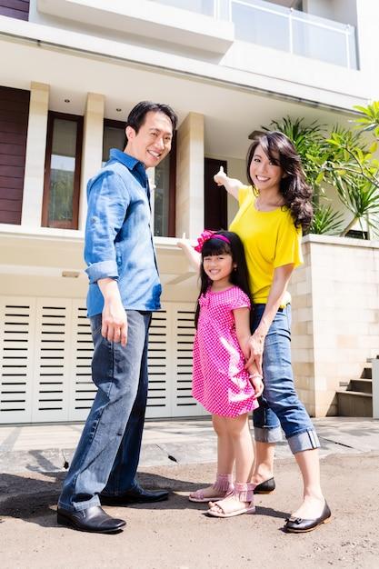Família chinesa na frente da casa Foto Premium